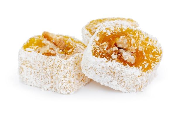 Gelber türkischer genuss mit nüssen in puderzucker lokalisiert auf weiß