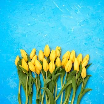 Gelber tulpenblumenstrauß auf hellem blau. strauß. textfreiraum, ansicht von oben.