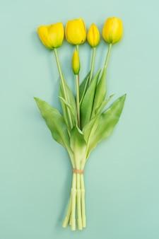 Gelber tulpenblumenstrauß auf minzhintergrund. flache lage, draufsicht