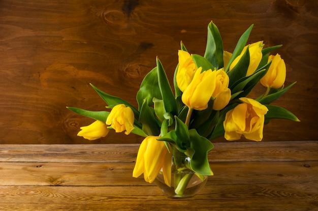Gelber tulpenblumenstrauß des frühlinges auf hölzernem hintergrund