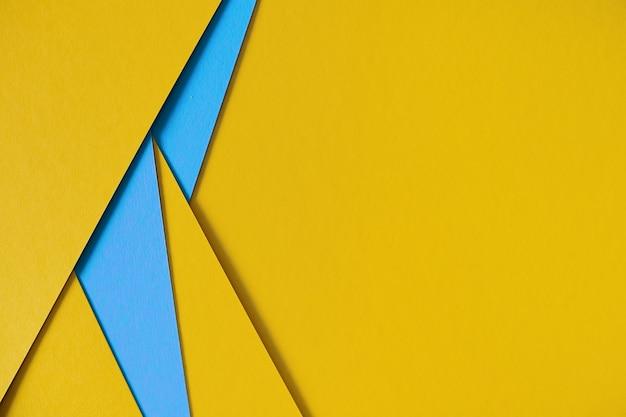 Gelber und blauer geometrischer zusammensetzungspappehintergrund mit copyspace
