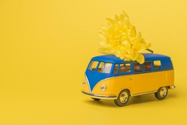 Gelber und blauer retro-spielzeugbus, der einen blumenstrauß von chrysanthemenblumen auf einem gelben hintergrund liefert. reisekonzept