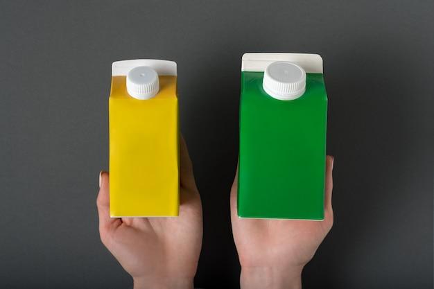 Gelber und grüner kartonkasten oder verpackung des tetrapacks in weibliche hände.