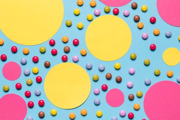 Gelber und rosa leerer kreisrahmen mit bunten edelstelsüßigkeiten auf blauem hintergrund