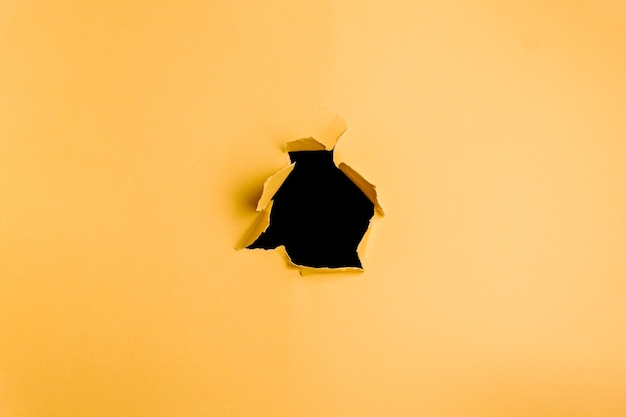 Gelber und schwarzer hintergrund des lochs im karton mit kopienraum