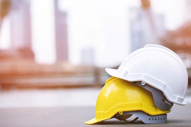 Gelber und weißer harter sicherheitshelmhut im projekt am baustellengebäude auf betonboden auf stadt mit sonnenlicht. helm für arbeiter als ingenieur oder arbeiter. konzeptsicherheit zuerst.