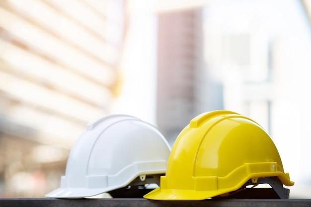 Gelber und weißer harter sicherheitshelmhut im projekt am baustellengebäude auf betonboden