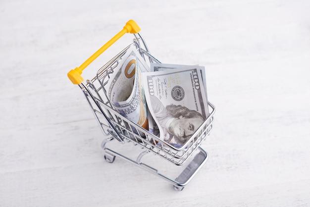 Gelber wagen mit einigen dollar, online-shopping-konzept