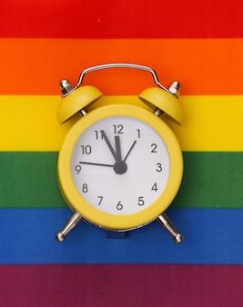 Gelber wecker auf einem regenbogenhintergrund. lgbt-flagge