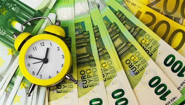 Gelber wecker und euro-banknoten unterschiedlicher stückelung