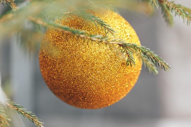 Gelber weihnachtsball, der am tannenbaum hängt