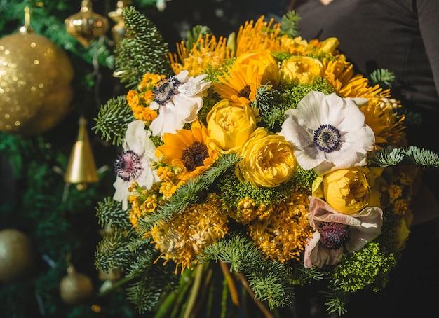Gelber winterblumenstrauß mit goldenen weihnachtsverzierungen