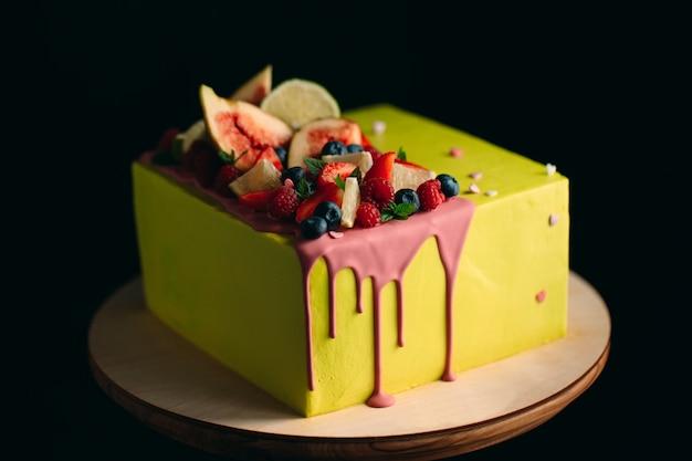 Gelber zitrusfruchtkuchen verziert mit feigen, himbeeren, blaubeeren und zitrone.