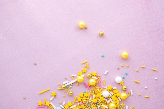 Gelber zucker streut körnig auf rosa hintergrund, nahaufnahme flach mit kopienraum.