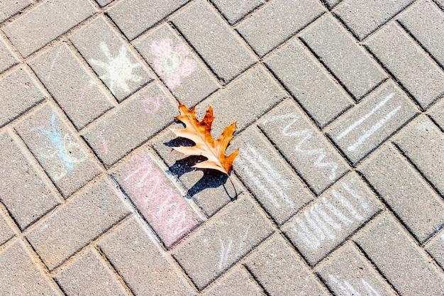 Gelbes ahornblatt auf den sideboardfliesen mit kreidezeichnungen für kinder. herbst im park.