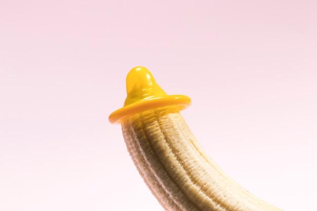 Gelbes ausgepacktes kondom auf einer banane