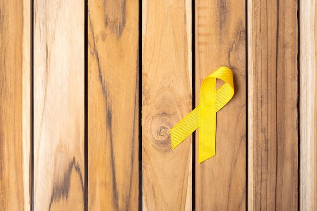 Gelbes band auf holztischhintergrund zur unterstützung von menschenleben und krankheit. september suizidpräventionstag, monat des bewusstseins für kinderkrebs und konzept des weltkrebstages