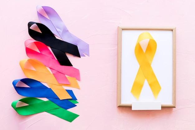 Gelbes band auf weißem holzrahmen nahe der reihe des bunten bewusstseinsbandes