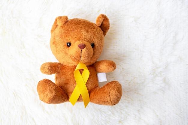 Gelbes band mit bärenpuppe auf weißem hintergrund zur unterstützung des lebens und der krankheit von kindern. september kinderkrebs-aufklärungsmonat und konzept zum weltkrebstag