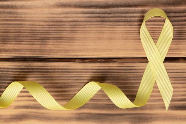 Gelbes bewusstseinsband, auf holztisch. sarkom. krebs im kindesalter. weltkrebstag. flach liegen. speicherplatz kopieren