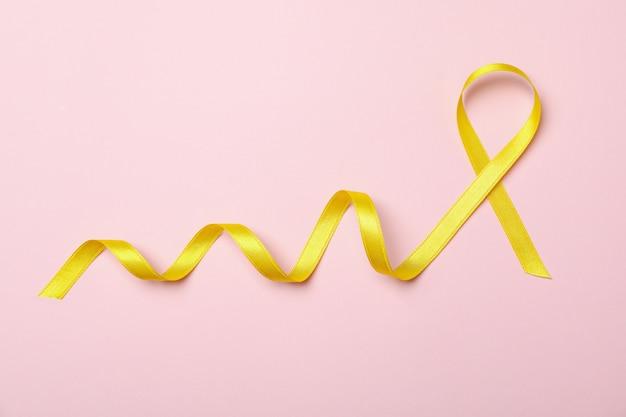 Gelbes bewusstseinsband auf rosa hintergrund, raum für text