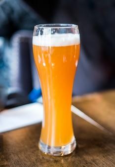 Gelbes bier vom fass mit schaum im glas