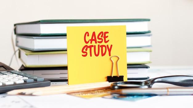 Gelbes blatt papier mit text fallstudie steht auf einem clip für papiere auf dem schreibtisch vor dem hintergrund gestapelter bücher, taschenrechner, kreditkarten. geschäfts- und finanzkonzept. selektiver fokus.