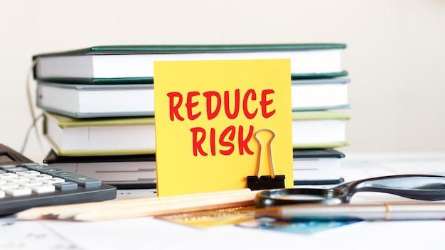Gelbes blatt papier mit text reduziert das risiko steht auf einem clip für papiere auf dem schreibtisch vor dem hintergrund von gestapelten büchern, taschenrechnern, kreditkarten. geschäfts- und finanzkonzept. selektiver fokus.