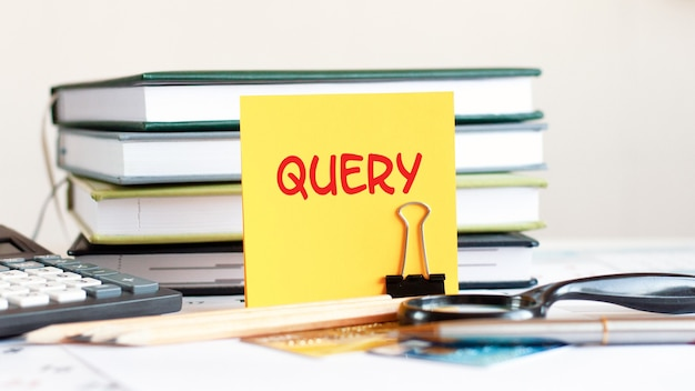 Gelbes blatt papier mit textabfrage steht auf einem clip für papiere auf dem schreibtisch vor dem hintergrund gestapelter bücher, taschenrechner, kreditkarten. geschäfts- und finanzkonzept. selektiver fokus.