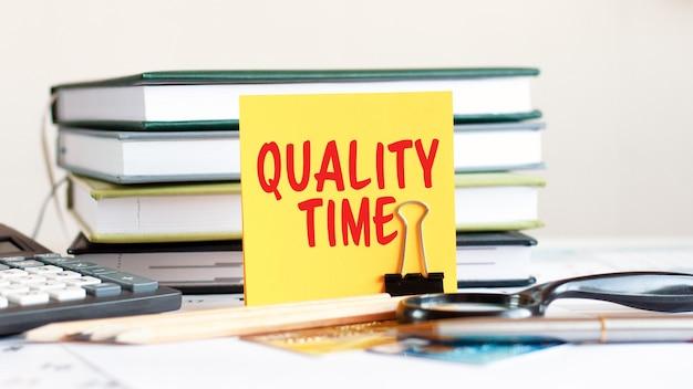 Gelbes blatt papier mit textqualitätszeit steht auf einem clip für papiere auf dem schreibtisch vor dem hintergrund von gestapelten büchern, taschenrechnern, kreditkarten. geschäfts- und finanzkonzept. selektiver fokus.