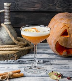 Gelbes cocktail mit orange auf dem tisch