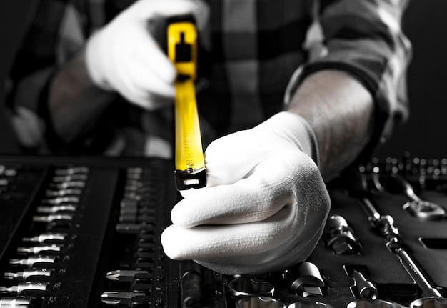 Gelbes einziehbares maßbandwerkzeug, das in männlichen händen in weißen handschuhen über dem werkzeugkasten auf die kamera ausgebreitet wird, nahaufnahme.