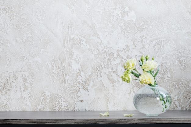 Gelbes eustoma in glasvase auf dem tisch