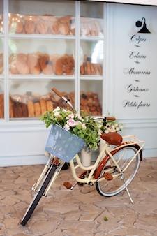 Gelbes fahrrad der weinlese mit einem korb mit blumen steht nahe dem café einer bäckerei vor dem hintergrund des hölzernen blauen hauses.