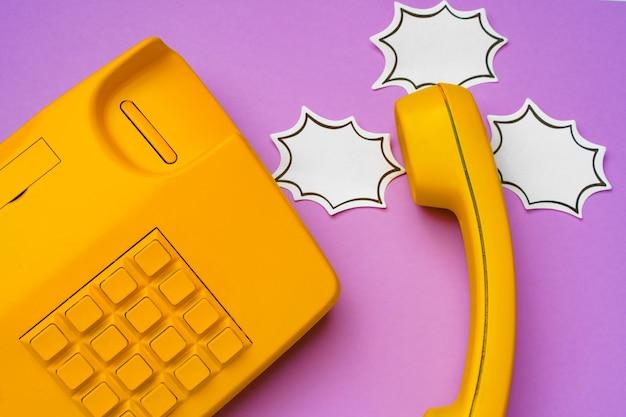 Gelbes festnetztelefon mit sprechblase auf lila oberfläche