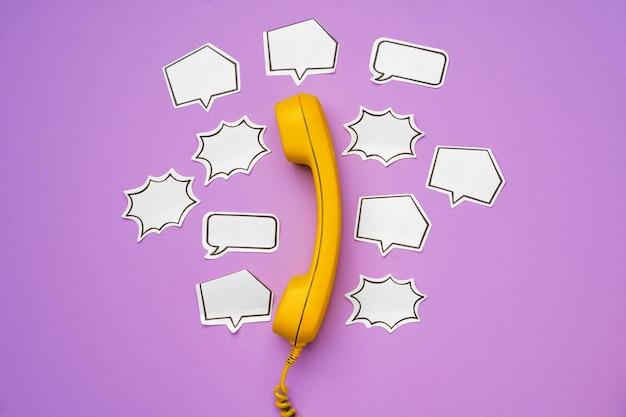 Gelbes festnetztelefon mit sprechblase auf lila