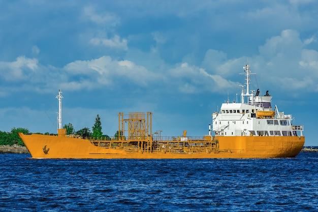 Gelbes frachttankerschiff, das sich am klaren sommertag bewegt