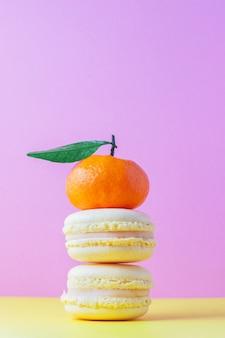 Gelbes französisches makronengebäck mit zitronencreme auf gelb und rosa mit orangefarbener mandarine