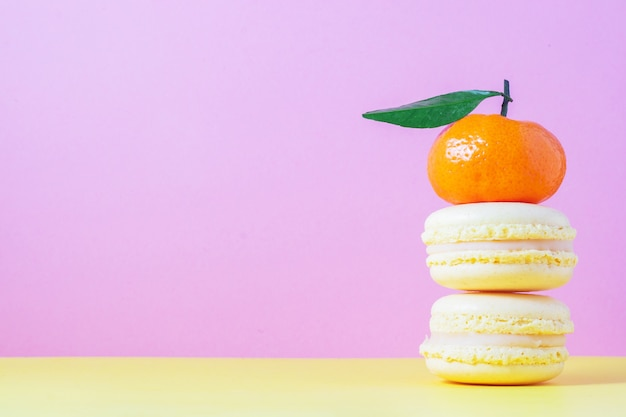 Gelbes französisches makronengebäck mit zitronencreme auf gelb und rosa mit vertikaler orangefarbener mandarine
