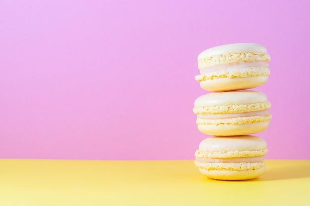 Gelbes französisches makronengebäck mit zitronencreme auf gelb und rosa