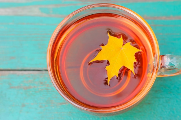Gelbes gefallenes herbstahornblatt in einer tasse tee. konzept der herbststimmung und des kanada-tages. atmosphäre herbstsaison im freien hintergrund