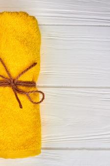 Gelbes gerolltes tuch auf weißem hölzernem schreibtischhintergrund. nahaufnahme vertikaler schuss.