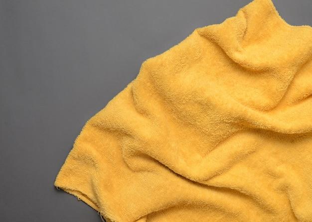 Gelbes handtuch auf grauem hintergrund. speicherplatz kopieren. draufsicht.
