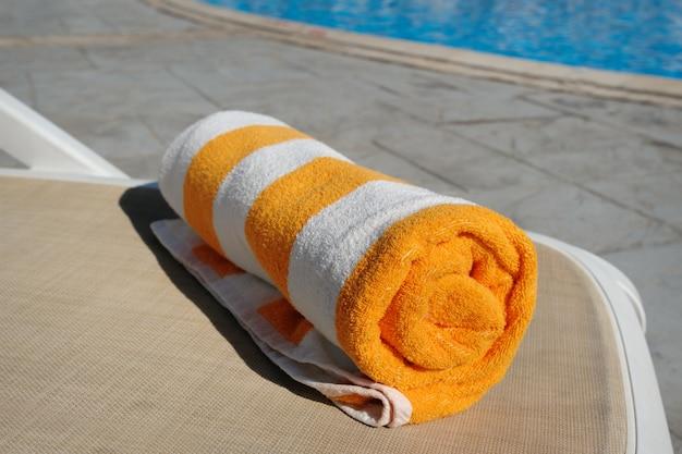 Gelbes handtuch, das auf einer liege neben dem schwimmbad liegt
