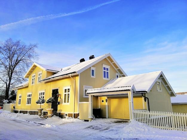 Gelbes haus umgeben von bäumen, die im schnee unter einem bewölkten himmel in larvik in norwegen bedeckt sind