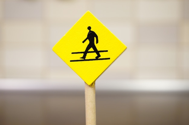 Gelbes hölzernes spielzeugzeichen mit einer gehenden personenikone