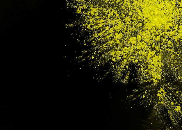 Gelbes holi pulver an der ecke der schwarzen oberfläche