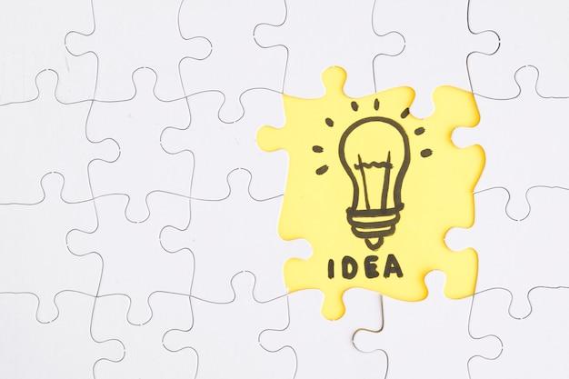 Gelbes ideenpuzzle stehen von den weißen stücken heraus