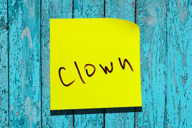 Gelbes klebriges blatt an der wand. inschrift marker wort clown
