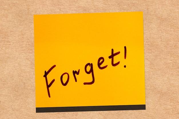 Gelbes klebriges blatt an der wand. inschrift marker wort vergessen